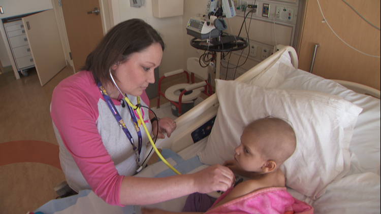Erika Rucks cares for Lucie Mertz, a three-year-old cancer patient