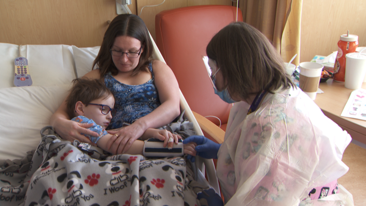 Nurse Erika Rucks holds the hand of William, one of her young patients.