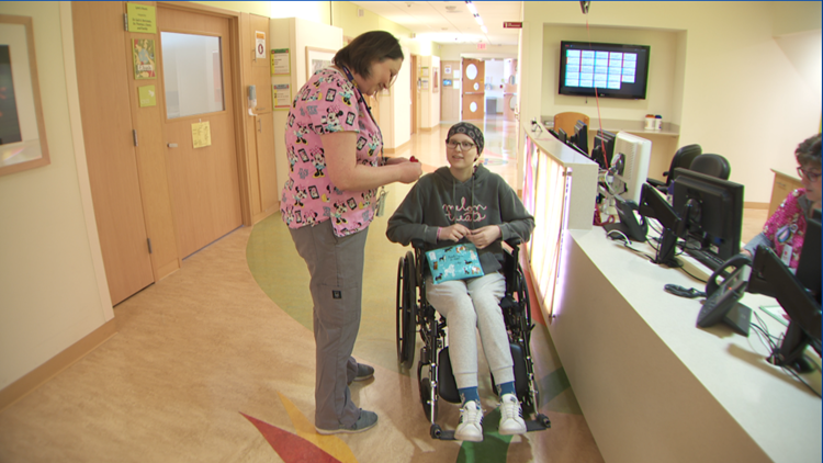 Nurse Erika Rucks spends a few minutes with Izzy Bogie, a 15-year-old cancer patient who has stopped to visit the nurses who treated her at U of M Ma