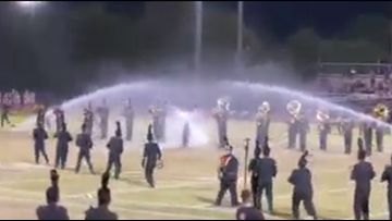 High school marching band continues performance through sprinkler interruption