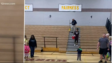 8th grader helps janitor clean the stands after school basketball game