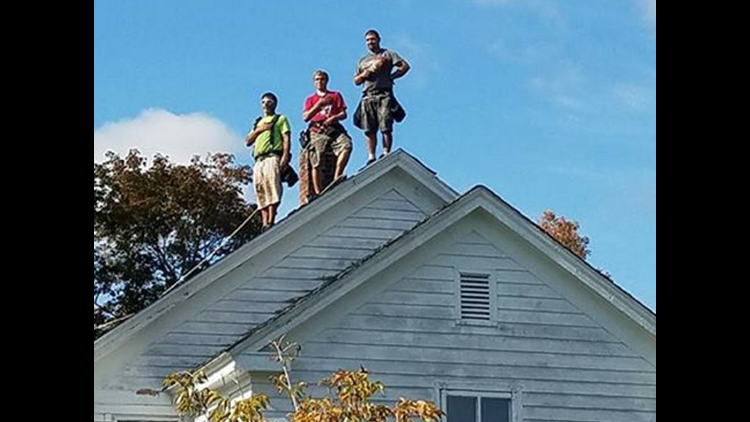 In themidst of the controversial debateon standing for the national anthem, a patriotic photo of three roofers is going viral.