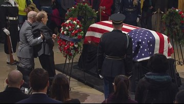 Former Senator Bob Dole stands to salute casket of George H.W. Bush