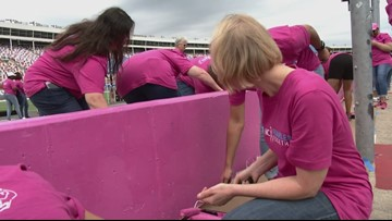 Breast cancer survivors paint pit road wall pink at Charlotte Motor Speedway